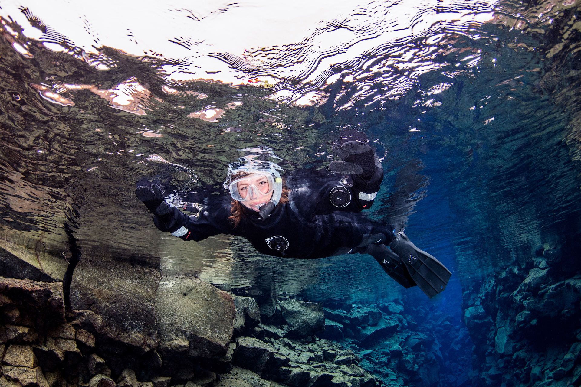 Happy Silfra snorkeler close up from beneath reflecting crystal water surface of Silfra hall in Thingvellir Iceland